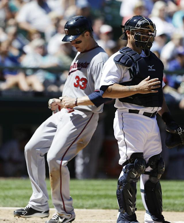Minnesota Twins' Justin Morneau (33) scores as Seattle Mariners catcher Humberto Quintero stands by in the fourth inning of a baseball game, Saturday, July 27, 2013, in Seattle. (AP Photo/Elaine Thompson)