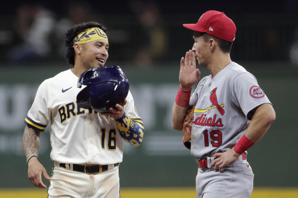 Milwaukee Brewers' Kolten Wong (16) laughs with St. Louis Cardinals' Tommy Edman (19) after hitting a double during the eighth inning of a baseball game Tuesday, Sept. 21, 2021, in Milwaukee. (AP Photo/Aaron Gash)