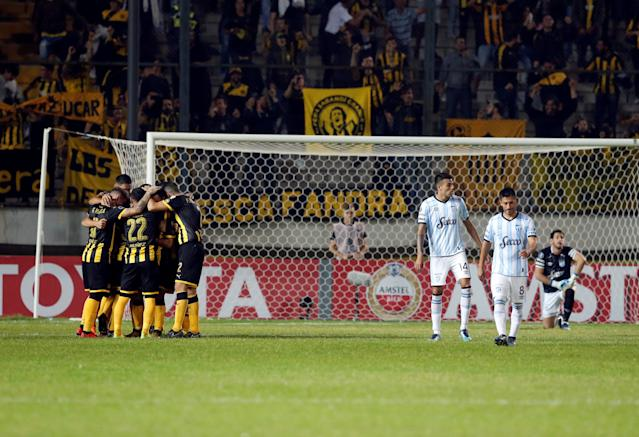 Soccer Football - Uruguay's Penarol v Argentina's Atletico Tucuman - Copa Libertadores - Campeon del siglo stadium, Montevideo, Uruguay - April 4, 2018. Penarol's Fabian Estoyanoff (obscured) is congratulated by teammates after scoring . REUTERS/Andres Stapff