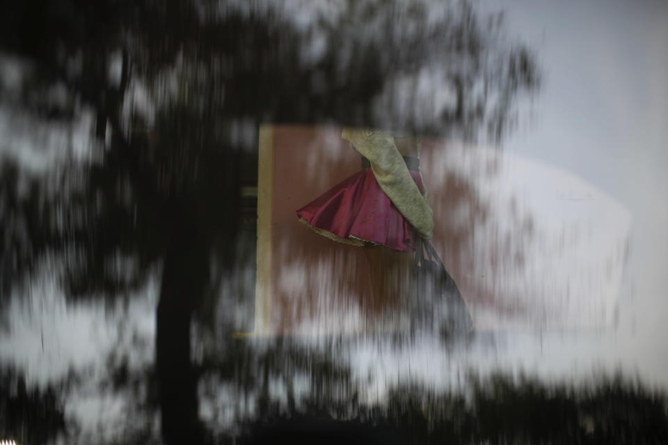 Sex worker Geraldine's skirt blows up in the breeze as she is seen through the reflective window of a parked car while waiting for clients near the Revolution subway station, in Mexico City, Thursday, March 25, 2021. Thousands of new sex workers have pushed onto the streets as the coronavirus pandemic forced the closure of restaurants and shops. (AP Photo/Rebecca Blackwell)