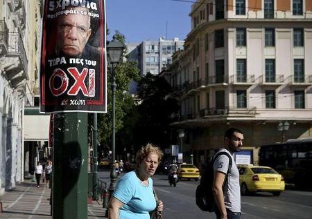 People stand next to a referendum campaign poster depicting German Finance Minister Wolfgang Schaeuble in Athens, Greece, July 2, 2015.  REUTERS/Alkis Konstantinidis