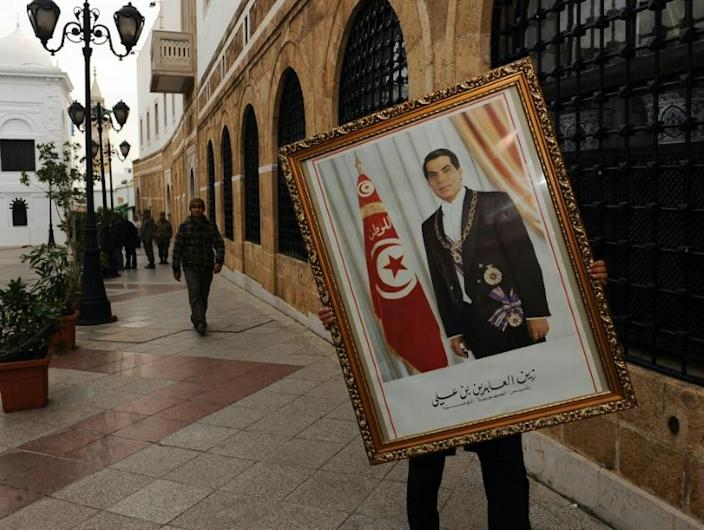 A Tunisian government employee removes a portrait of Ben Ali in January 2011, days after the longtime dictator was forced from power, triggering revolts across the Arab world (AFP Photo/FETHI BELAID)