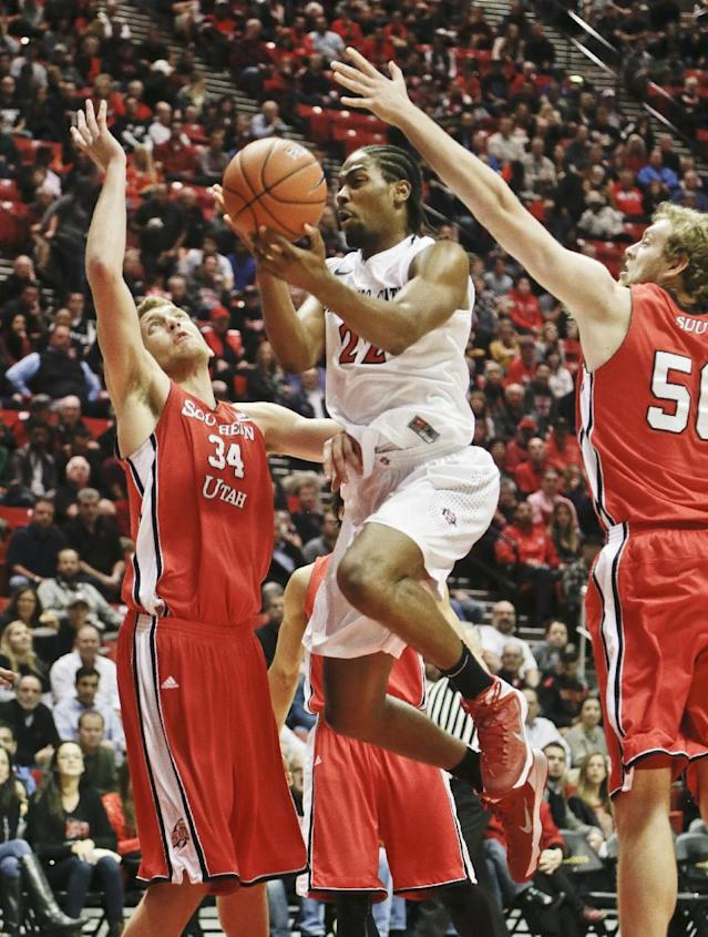 San Diego State forward Josh Davis splits Southern Utah defenders Cal Hanks, left, and Jayson Cheesman while scoring during the first half of an NCAA college basketball game Wednesday, Dec. 18, 2013, in San Diego. (AP Photo/Lenny Ignelzi)