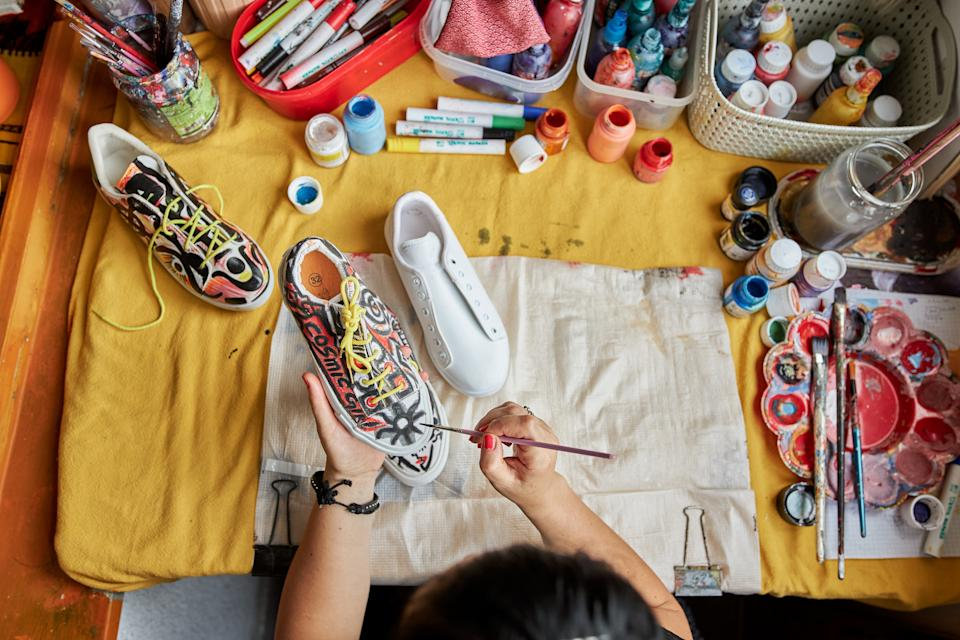 Mid adult female alternative artist painitng on a sneakers in her messy workshop at balcony