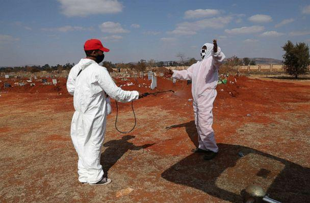 PHOTO: Funeral workers wearing personal protective equipment sanitize each other after a burial at the Olifantsvlei cemetery, south-west of Johannesburg, South Africa, on July 28, 2020, during a nationwide lockdown amid the coronavirus pandemic. (Siphiwe Sibeko/Reuters)