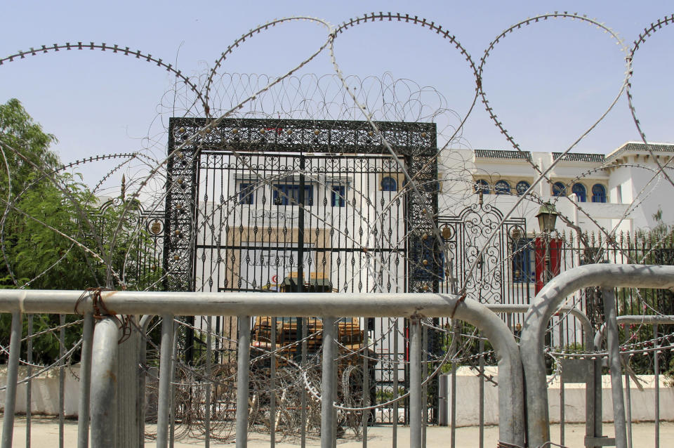 Barbed wire and a military armored personnel carrier block a side entrance of the Tunisian parliament in Tunis, Tuesday, July 27, 2021. The Ennahda party, has called for dialogue, following President Kais Saeid's sacking of the prime minister and suspension of parliament on Sunday. (AP Photo/Hassene Dridi)