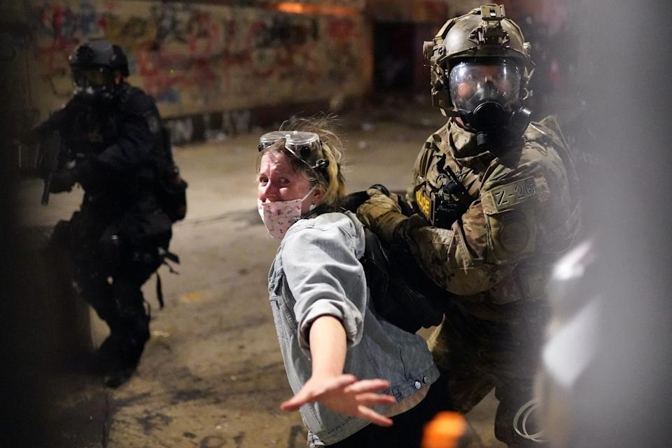 """Federal officers arrest a protester after she crossed a fence line set up around the federal courthouse building in downtown Portland on July 23, 2020. <p class=""""copyright""""><a href=""""https://www.gettyimages.com/detail/news-photo/federal-officers-arrest-a-protester-after-she-crossed-a-news-photo/1227747899?adppopup=true"""" rel=""""nofollow noopener"""" target=""""_blank"""" data-ylk=""""slk:Nathan Howard/Getty Images"""" class=""""link rapid-noclick-resp"""">Nathan Howard/Getty Images</a></p>"""