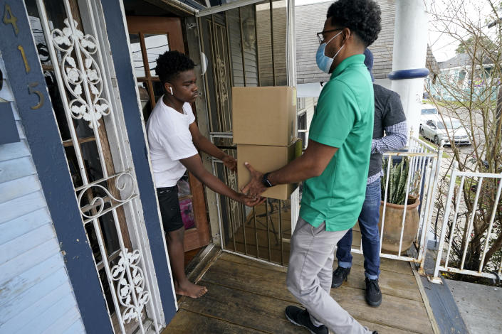 """David Russ, left, receives boxes of meals for his grandparents from Courtney Jones of Revolution Foods in New Orleans on Thursday, Feb. 11, 2021. """"We've had quite a few people tell us that they would not have meals, they literally would not have food if not for the program,"""" said Darnell Head, of Revolution Foods, which operates the program in New Orleans. (AP Photo/Gerald Herbert)"""