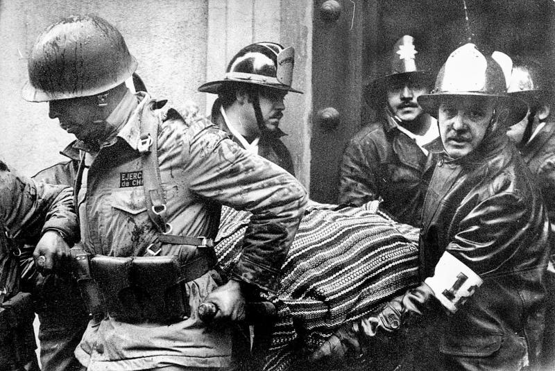 FILE - Soldiers and firefighters carry the body of President Salvador Allende, wrapped in a Bolivian poncho, out of the destroyed La Moneda presidential palace after the Sept. 11, 1973 coup led by Gen. Augusto Pinochet that ended Allende's three-year government. On Tuesday, Sept. 11, 2012, a Chilean court closed the judicial investigation into the death of Allende, confirming that the president committed suicide to avoid falling into the hands of the military coup led by Augusto Pinochet. (AP Photo/El Mercurio, File) CHILE OUT - NO PUBLICAR EN CHILE