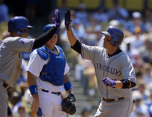 As Los Angeles Dodgers catcher A.J. Ellis, center, looks on Colorado Rockies' Michael Cuddyer, right, is congratulated by teammate Carlos Gonzalez, left, after hitting a two-run home run during the fifth inning of their baseball game on Sunday, July 14, 2013, in Los Angeles. (AP Photo/Mark J. Terrill)