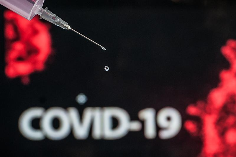 This photo illustration show a syringe referring to the vaccine for fighting the coronavirus (COVID-19), with a representation of the virus in the background, photographed In Rio de Janeiro, Brazil, on July 15, 2020. The Brazilian government announced agreements with the University of Oxford, in the United Kingdom, and with the Chinese company Sinovac and continues with the tests of the vaccine against Coronavirus (COVID-19) here in Brazil and may have its registration released in June 2021. (Photo Illustration by Allan Carvalho/NurPhoto via Getty Images)