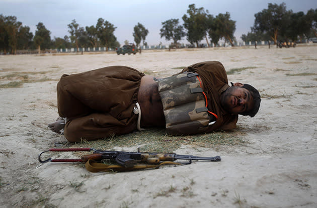 A suicide bomber lies on the ground, his hands tied behind his back, after a bomb expert defused his explosive vest. (Parwiz/Reuters)