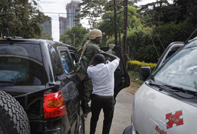 A member of Kenyan special forces is helped out of a US embassy diplomatic vehicle by a paramedic at the scene Wednesday, Jan. 16, 2019 in Nairobi, Kenya. Extremists stormed a luxury hotel in Kenya's capital on Tuesday, setting off thunderous explosions and gunning down people at cafe tables in an attack claimed by Africa's deadliest Islamic militant group. (AP Photo/Ben Curtis)
