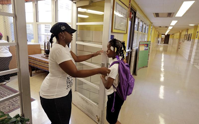 "Crystal Stoval delivers her niece Kayla Porter to Gresham Elementary School on the first day of classes Monday, Aug. 26. 2013 in Chicago. The school that Kayla attended last year was closed over the summer by Chicago Public Schools. Thousands of students will walk newly designated ""Safe Passage"" routes after CPS announced in May it would close about 50 schools and programs. Workers hired to help students get to and from school safely will be stationed along those routes, as well as police, firefighters and even public library security guards. (AP Photos/M. Spencer Green)"