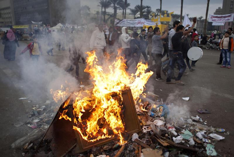Protesters opposed to Egyptian President Mohammed Morsi chant slogans near burning garbage at Tahrir Square in Cairo, Egypt, Wednesday, Dec. 5, 2012. Supporters and opponents of Egyptian leader Mohammed Morsi fought with rocks, firebombs and sticks outside the presidential palace in Cairo on Wednesday, as a new round of protests deepened the country's political crisis. (AP Photo/Nasser Nasser)