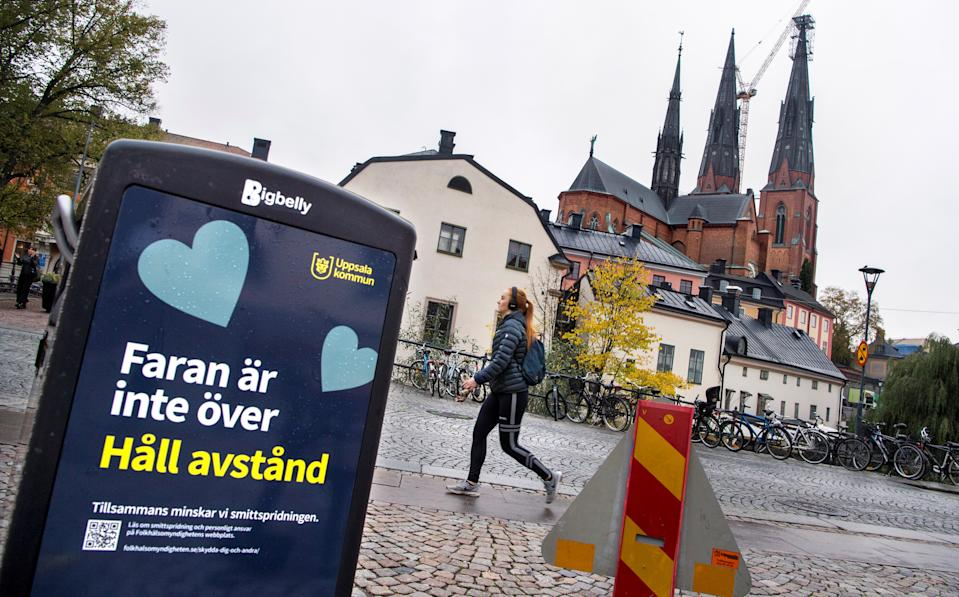 "A woman walks near a trash can with a sign reading ""The danger is not over - Keep your distance"" on a pedestrian street as the coronavirus disease (COVID-19) outbreak continues in Uppsala, Sweden October 21, 2020. TT News Agency/Claudio Bresciani via REUTERS      ATTENTION EDITORS - THIS IMAGE WAS PROVIDED BY A THIRD PARTY. SWEDEN OUT."