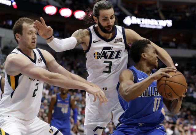Utah's Joe Ingles and Ricky Rubio swarm Mavs guard Yogi Ferrell on Thursday night. (AP)