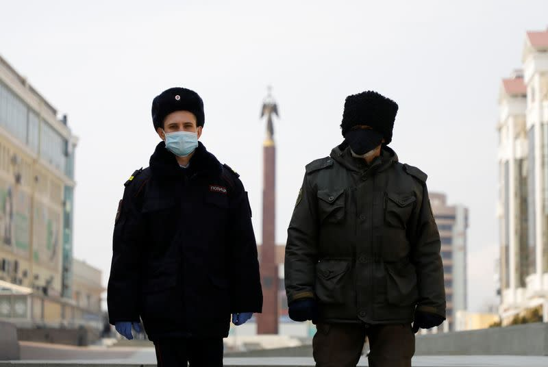 A police officer and a cossack wearing protective masks patrol the territory in Stavropol