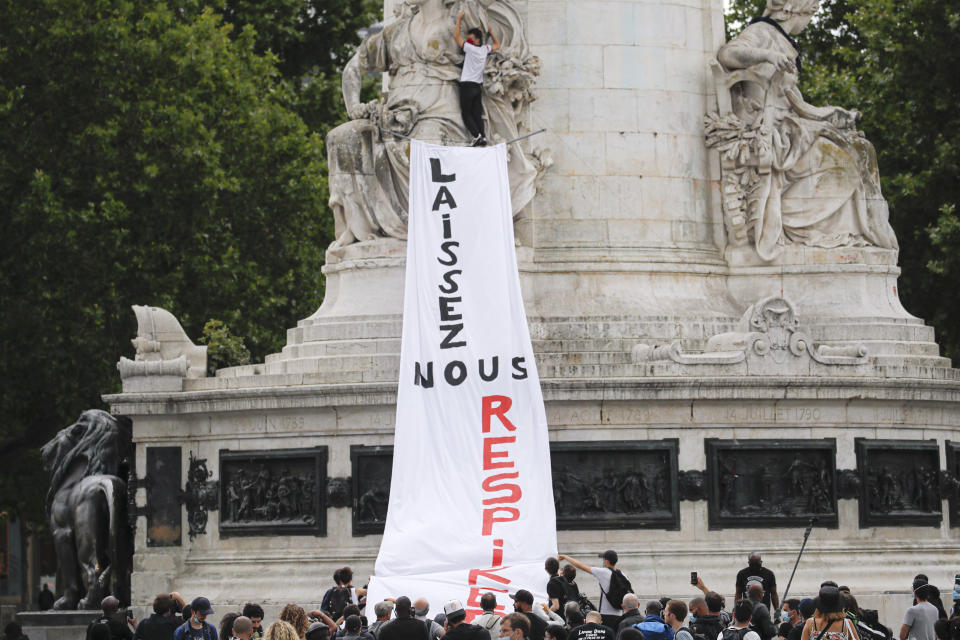 """People hang a banner thet reads """"Let us breathe"""" on a statue during a protest in memory of Lamine Dieng, a 25-year-old Franco-Senegalese who died in a police van after being arrested in 2007, in Paris, Saturday, June 20, 2020. Multiple protests are taking place in France on Saturday against police brutality and racial injustice, amid weeks of global anger unleashed by George Floyd's death in the US. (AP Photo/Christophe Ena)"""