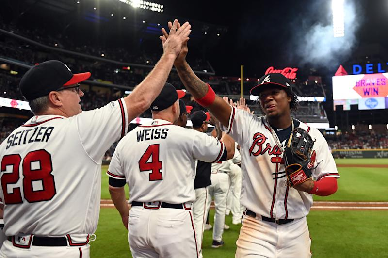 Sep 21, 2019; Cumberland, GA, USA; Atlanta Braves center fielder Ronald Acuna Jr. (13) high fives Atlanta Braves hitting coach Kevin Seitzer (28) after defeating the San Francisco Giants at SunTrust Park. Mandatory Credit: Adam Hagy-USA TODAY Sports