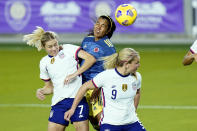 Colombia defender Daniela Arias, center, tries to head the ball to the goal off a corner kick as she is defended by United States defender Abby Dahlkemper (7) and midfielder Lindsey Horan (9) during the first half of an international friendly soccer match, Monday, Jan. 18, 2021, in Orlando, Fla. (AP Photo/John Raoux)