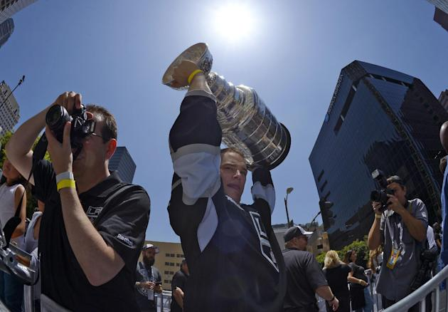 Los Angeles Kings right wing Dustin Brown,center, holds up the Stanley Cup trophy while riding in a parade, Monday, June 16, 2014, in Los Angeles. The parade and rally were held to celebrate the Kings' second Stanley Cup championship in three seasons. The Kings defeated the New York Rangers for the title. (AP Photo/Mark J. Terrill)