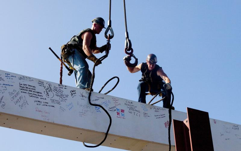 """FILE - In this file photo of Aug. 2, 2012, ironworkers James Brady, left, and Billy Geoghan release the cables from a steel beam after connecting it on the 104th floor of One World Trade Center in New York. The beam was signed by President Barack Obama with the notes: """"We remember,"""" ''We rebuild"""" and """"We come back stronger!"""" during a ceremony at the construction site June 14. Also adorned with the autographs of workers and police officers at the site, the beam will be sealed into the structure of the tower, which is scheduled for completion in 2014. (AP Photo/Mark Lennihan, File)"""