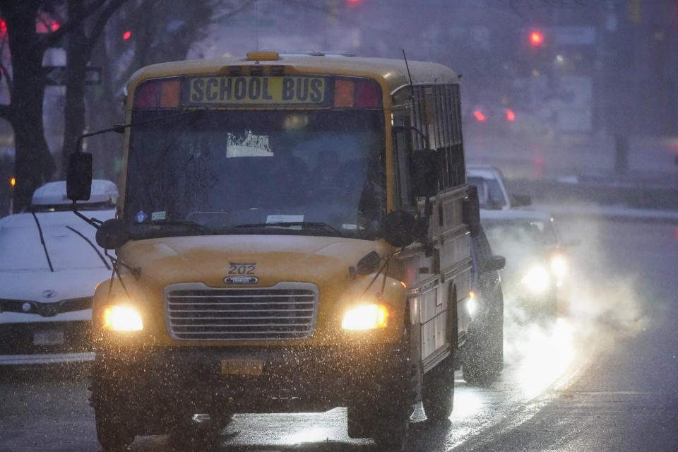 A school bus moves after dropping off students in the Queens borough of New York as snow starts to fall, Wednesday, Dec. 16, 2020. (AP Photo/Frank Franklin II)