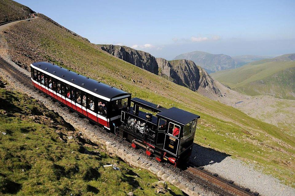 """<p>When it comes to impressive views, Wales' <a href=""""https://www.goodhousekeeping.com/uk/lifestyle/travel/a29696924/mount-snowdon-train-1/"""" rel=""""nofollow noopener"""" target=""""_blank"""" data-ylk=""""slk:Snowdon Mountain Railway"""" class=""""link rapid-noclick-resp"""">Snowdon Mountain Railway</a> certainly delivers. Offering a marvellous train holiday in the UK, this is where you can experience Mount Snowdon at its finest - from the top! </p><p>Departing from Llanberis, you'll be lifted 1,085 metres above sea level for the ride of your life.</p><p>One of the best parts is passing over the beautiful Afon Hwch river, where the Ceunant Mawr Waterfall plunges into the gorge below.</p><p><strong>Ride the Snowdon Mountain Railway during a Welsh rail holiday with Good Housekeeping, where you will also experience the Welsh Highland Railway and Ffestiniog Railway, from £625 per person.</strong> </p><p> <a class=""""link rapid-noclick-resp"""" href=""""https://www.goodhousekeepingholidays.com/tours/wales-by-heritage-rail-holiday"""" rel=""""nofollow noopener"""" target=""""_blank"""" data-ylk=""""slk:FIND OUT MORE"""">FIND OUT MORE</a></p><p><strong>We want to help you plan your next getaway with the experts. Sign up for the latest travel tales and to hear about our favourite financially protected escapes and bucket list adventures. </strong><a class=""""link rapid-noclick-resp"""" href=""""https://hearst.emsecure.net/optiext/optiextension.dll?ID=Mf2Mbm2t6kFIB2qaqu7QV5QAIooPPMrcO%2BU6d2SmsL4zpSgeyQIbzx5P9sbmxMKLhPooFIrsXaC2MY"""" rel=""""nofollow noopener"""" target=""""_blank"""" data-ylk=""""slk:SIGN UP"""">SIGN UP</a></p>"""