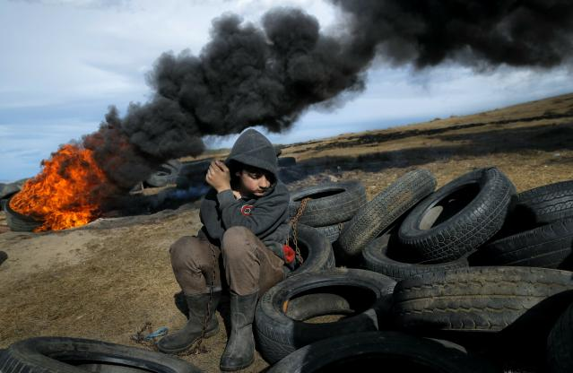 In this photo taken on Sunday, March 10, 2019, a boy pauses during a ritual marking the upcoming Clean Monday, the beginning of the Great Lent, 40 days ahead of Orthodox Easter, on the hills surrounding the village of Poplaca, in central Romania's Transylvania region. Romanian villagers burn piles of used tires then spin them in the Transylvanian hills in a ritual they believe will ward off evil spirits as they begin a period of 40 days of abstention, when Orthodox Christians cut out meat, fish, eggs, and dairy. (AP Photo/Vadim Ghirda)