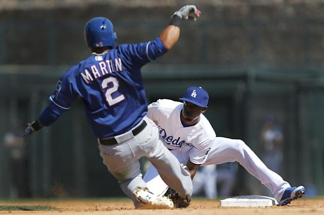 Los Angeles Dodgers second baseman Dee Gordon, right, tags out Texas Rangers' Leonys Martin who was attempting to steal second during a spring exhibition baseball game in Glendale, Ariz., Friday, March 7, 2014. (AP Photo/Paul Sancya)