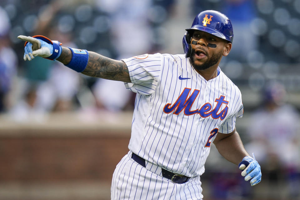 New York Mets' Dominic Smith gestures to his teammates after hitting a walkoff RBI-single during the eighth inning of the first baseball game of a doubleheader against the Philadelphia Phillies, Friday, June 25, 2021, in New York. (AP Photo/Frank Franklin II)