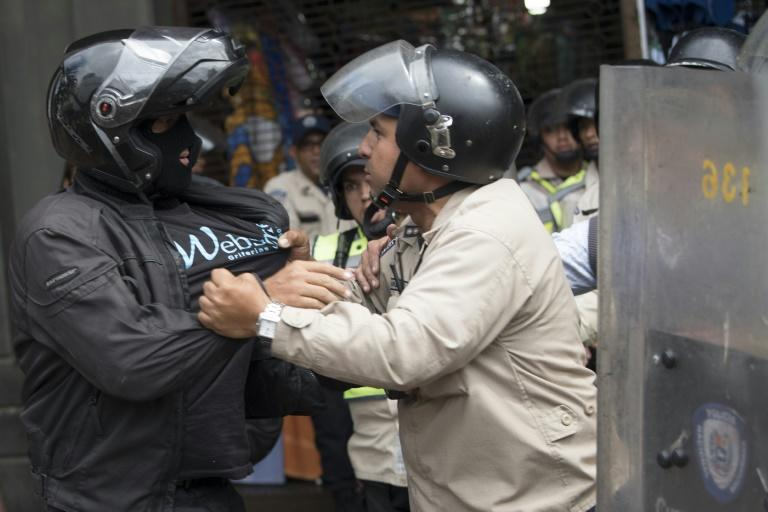 A Venezuelan pro-government supporter scuffles with riot police in Caracas, on March 31, 2017