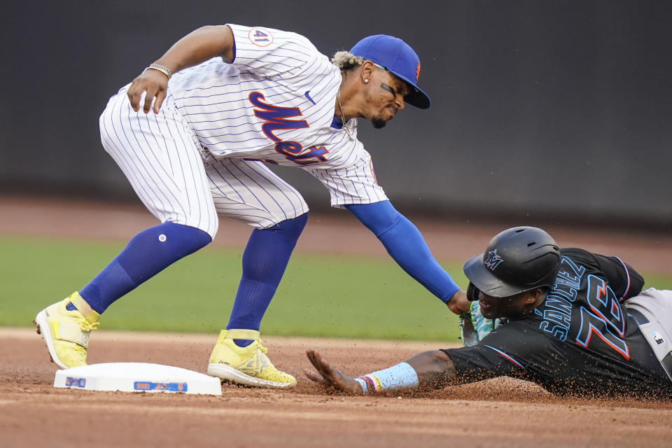 New York Mets' Francisco Lindor, left, tags out out Miami Marlins' Jesus Sanchez as he attempts to steal second base during the first inning in the first baseball game of a doubleheader Tuesday, Sept. 28, 2021, in New York. (AP Photo/Frank Franklin II)
