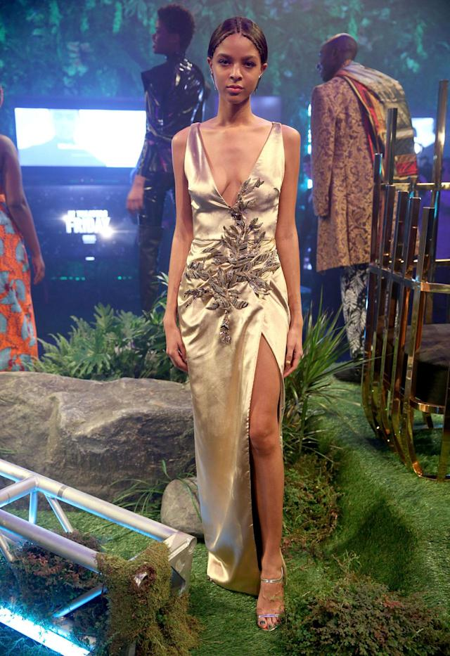 <p>Model wears a gold, velvety embellished dress by Cushnie et Ochs at the Black Panther Welcome to Wakanda NYFW fashion presentation. (Photo: Courtesy of Marvel Studios Black Panther/Getty) </p>