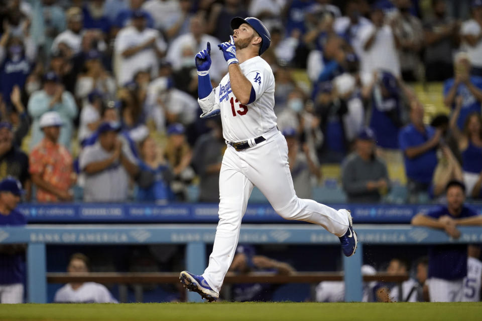 Los Angeles Dodgers' Max Muncy points skyward as he reaches home plate following his solo home run during the first inning of a baseball game against the Atlanta Braves, Monday, Aug. 30, 2021, in Los Angeles. (AP Photo/Marcio Jose Sanchez)