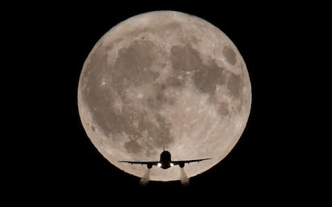 A passenger plane, with a full Harvest moon seen behind, makes its final landing approach towards Heathrow Airport - Credit: Reuters