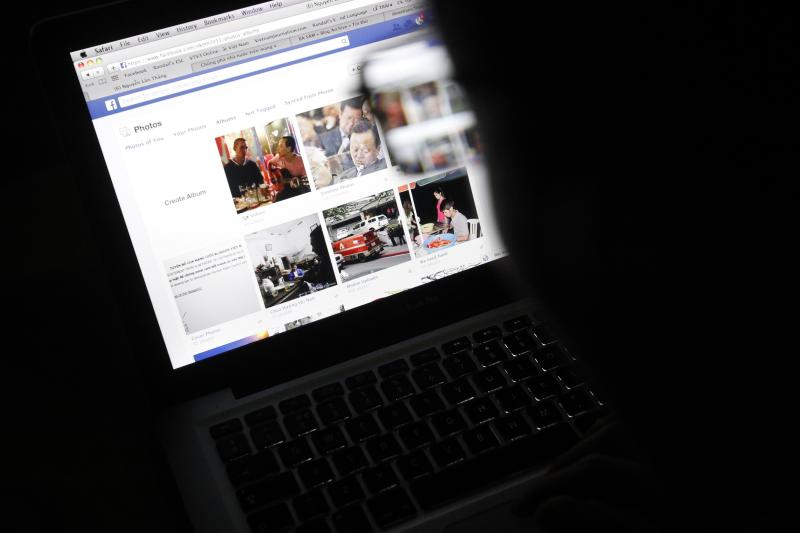 Vietnamese Internet activist Nguyen Lan Thang looks at a Facebook page at a cafe in Hanoi