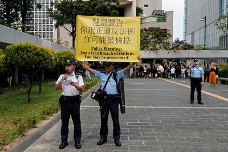 A policeman holds a sign while another warns people marching to protest against what they say is the abuse of pro-democracy protesters by Hong Kong police, at Chater Garden in Central district, Hong Kong