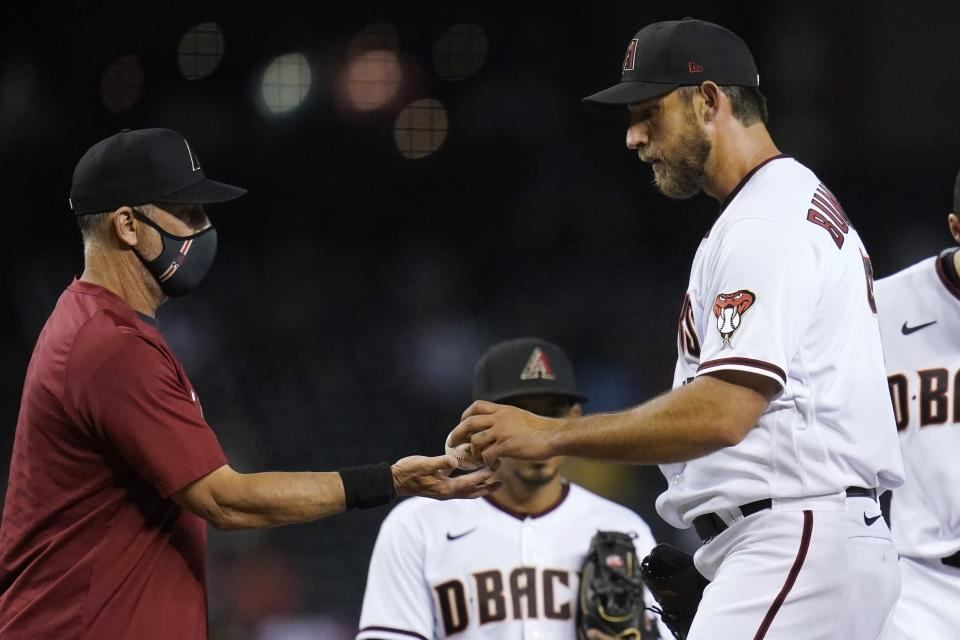 Arizona Diamondbacks starting pitcher Madison Bumgarner, right, hands the baseball over to manager Torey Lovullo as Bumgarner is taken out of the game during the fifth inning of a baseball game against the Oakland Athletics Monday, April 12, 2021, in Phoenix. (AP Photo/Ross D. Franklin)