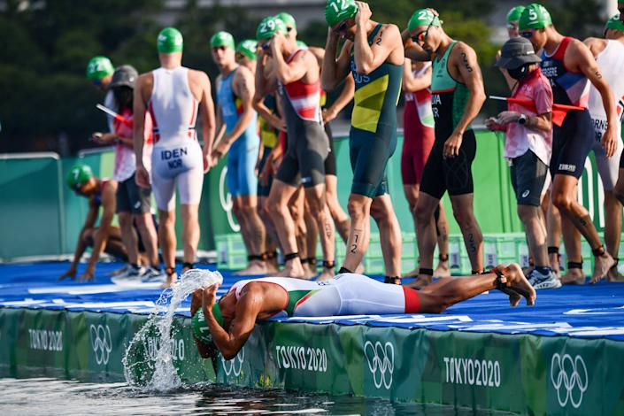<p>Athletes prepare to compete in the men's individual triathlon competition during the Tokyo 2020 Olympic Games at the Odaiba Marine Park in Tokyo on July 26, 2021. (Photo by Loic VENANCE / AFP)</p>