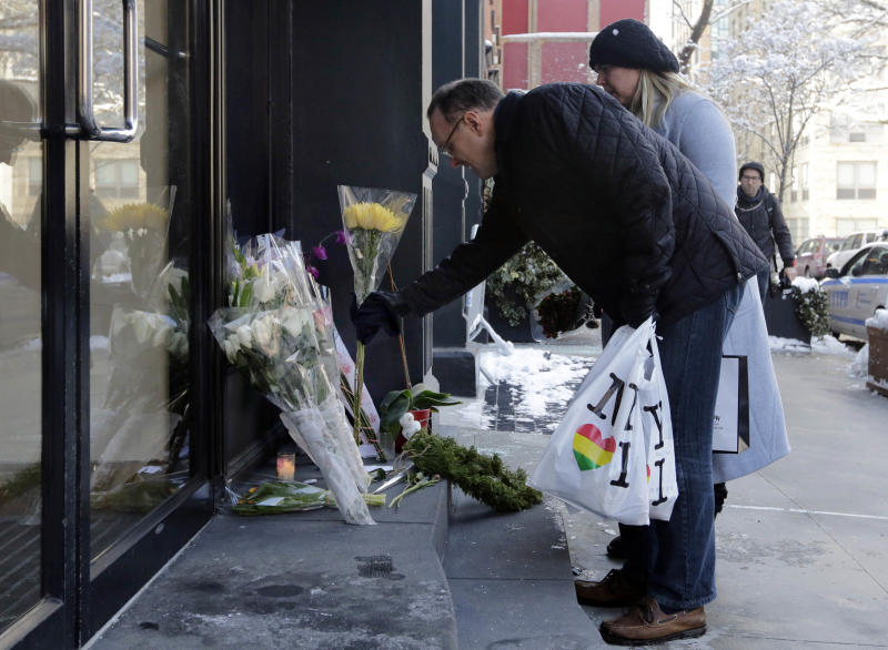A couple adds to the flowers placed outside the apartment building of actor Phillip Seymour Hoffman, in New York, Tuesday, Feb. 4, 2014. Autopsy results are expected soon in the death of actor Phillip Seymour Hoffman but police say it may take longer to determine if the heroin found in his apartment contains additives designed intensify the high. (AP Photo/Richard Drew)