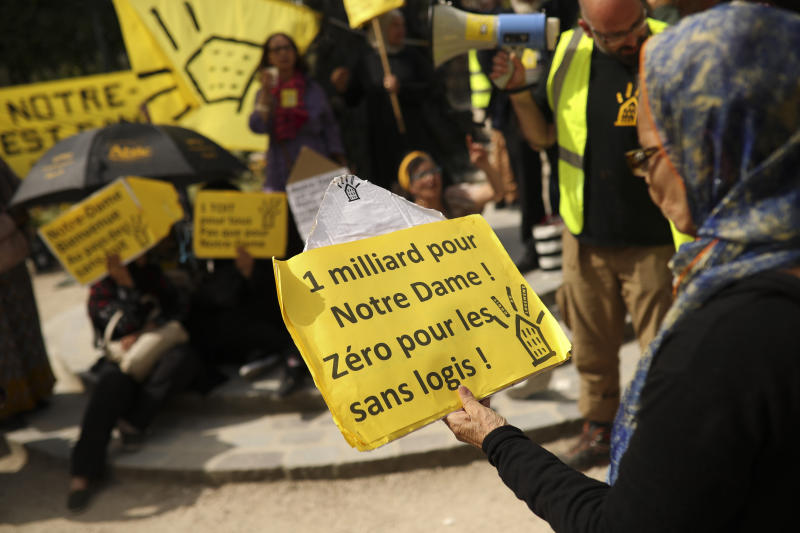 """A woman holds a poster that reads in French: """"One billion for Notre Dame! Zero for homeless"""" during a protest in front of the Notre Dame cathedral in Paris, Monday, April 22, 2019. (AP Photo/Francisco Seco)"""