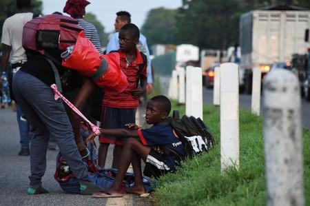 Migrants take a break as they walk along a road in a caravan towards the United States, in Tapachula