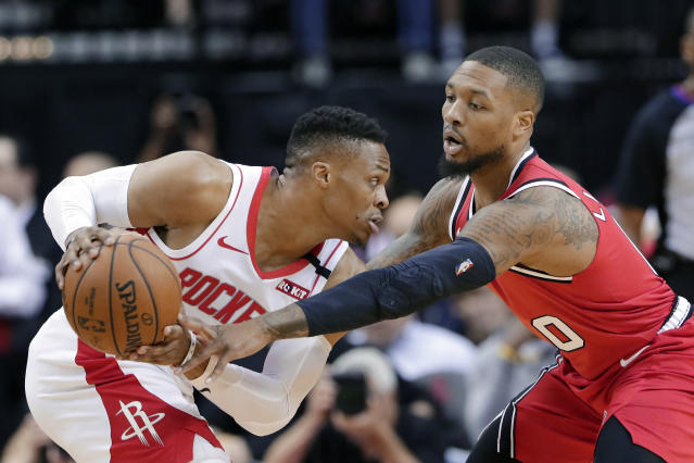 Houston Rockets guard Russell Westbrook (0) looks for a shot as Portland Trail Blazers guard Damian Lillard (0) reaches in during the first half of an NBA basketball game Wednesday, Jan. 15, 2020, in Houston. (AP Photo/Michael Wyke)