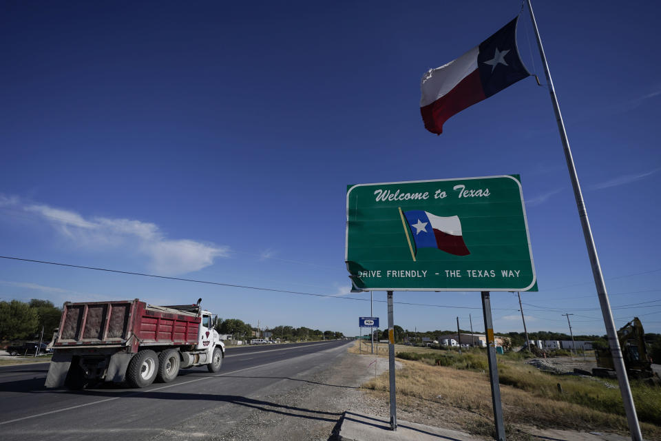 """A dump truck drives by a """"Welcome to Texas"""" near the Del Rio International Bridge, which remains closed due to a migrant encampment alongside the bridge, Friday, Sept. 24, 2021, in Del Rio, Texas.The """"amistad,"""" or friendship, that Del Rio, Texas, and Ciudad Acuña, Mexico, celebrate with a festival each year has been important in helping them deal with the challenges from a migrant camp that shut down the border bridge between the two communities for more than a week. (AP Photo/Julio Cortez)"""