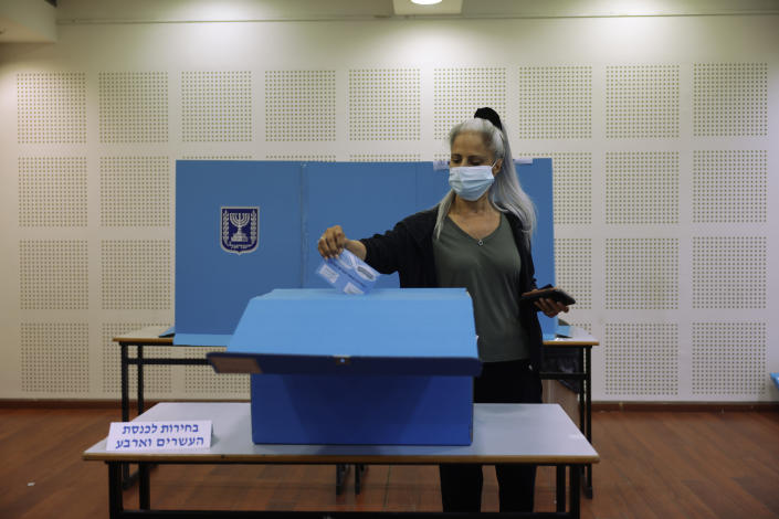 A woman votes for Israel's parliamentary election at a polling station in Ra'anana, Israel, Tuesday, March. 23, 2021. Israel is holding its fourth election in less than two years. (AP Photo/Tsafrir Abayov)