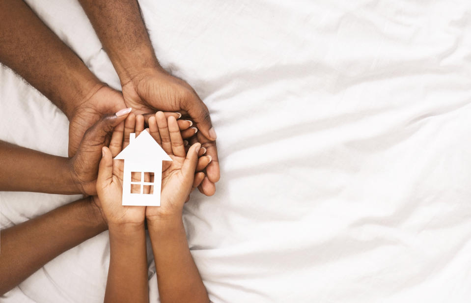 Adoption and family housing concept. Cutout paper house in hands of african american family over white bed sheet background. Closeup, panorama