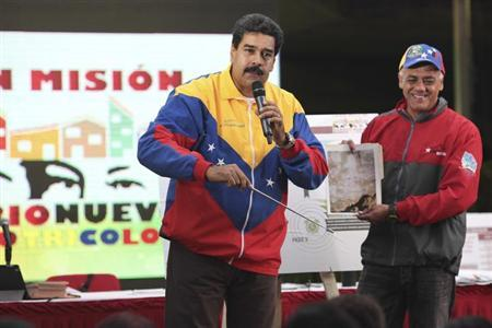Venezuela's President Nicolas Maduro (L) shows a picture of a metro tunnel wall with an image which he says is the face of late President Hugo Chavez, in Caracas October 30, 2013.
