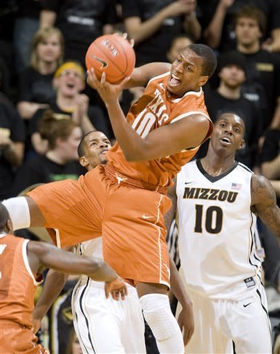 Texas' Jonathan Holmes, center, pulls down a rebound in front of Missouri's Ricardo Ratliffe, right, and Kim English, left, during the first half of an NCAA college basketball game Saturday, Jan. 14, 2012, in Columbia, Mo. (AP Photo/L.G. Patterson)